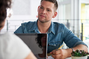 Image of two succesful business people using a laptop during conversation