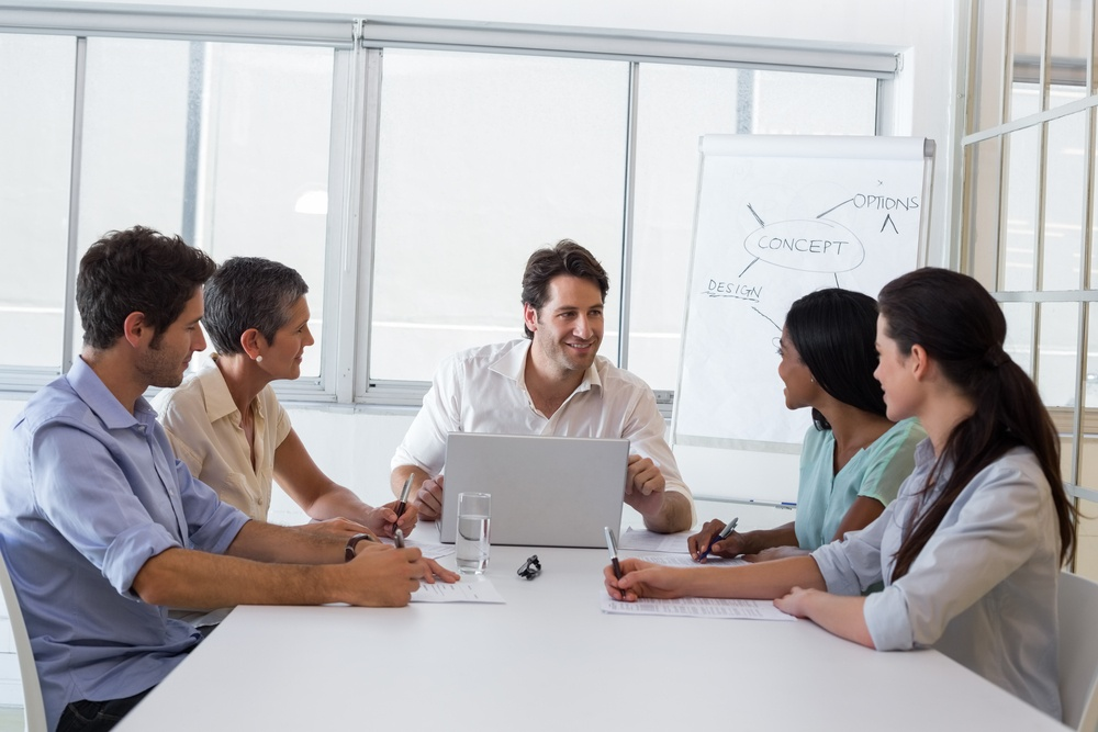 Attractive businessman speaking with fellow coworkers