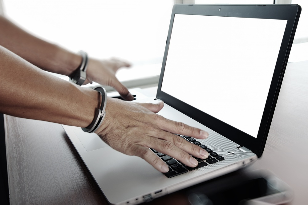 Businessman hand in handcuffs at wooden desk with laptop computer and digital tablet and stylus pen and smart phone as Cyber-Crime concept