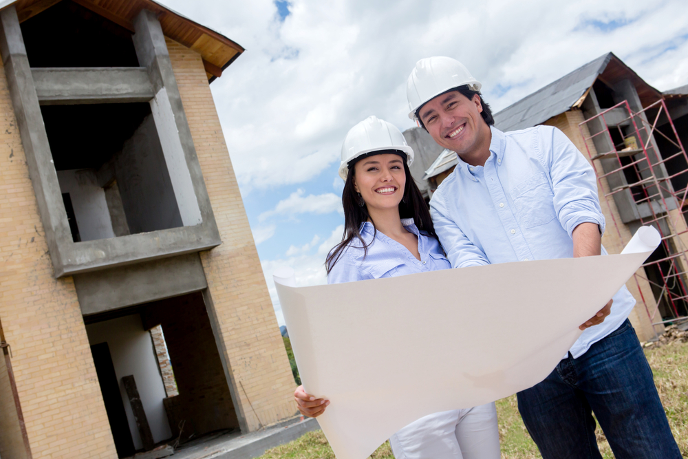 Couple holding blueprints of their new house