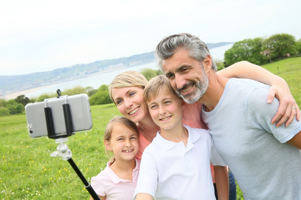 Family in vacation taking selfie picture with smartphone