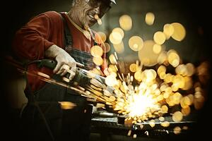 Industrial worker cutting and welding metal with many sharp sparks