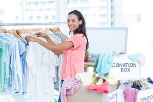 Portrait of a smiling young female volunteer separating clothes