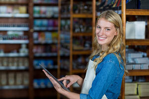 Portrait of smiling female staff using digital tablet in super market