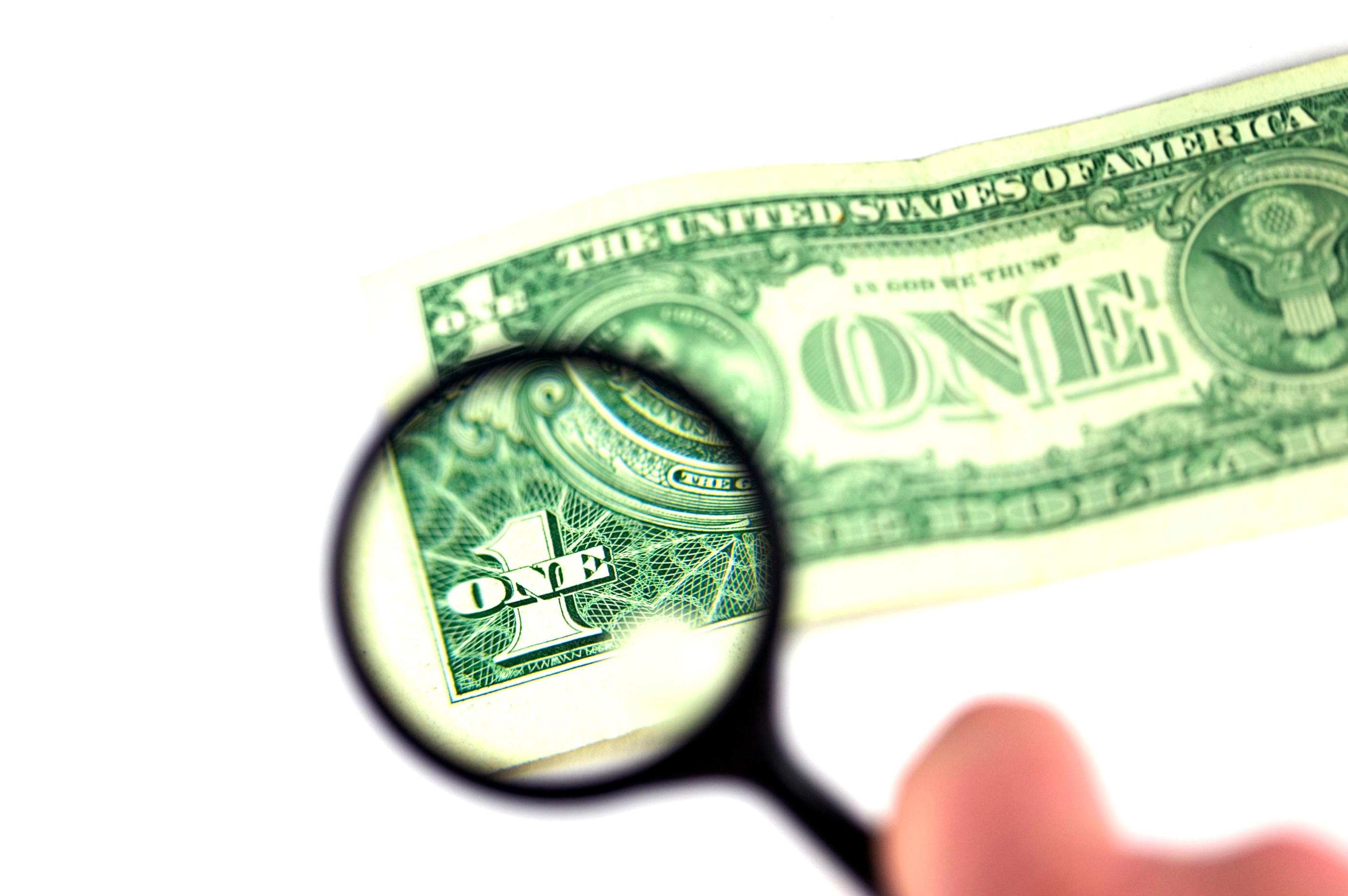 stockfresh_215083_examine-the-dollar_sizeM.jpg